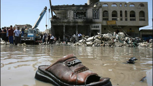 A mule is seen on the water in front of the ruins in the Shiite-dominated neighborhood of Amil, Baghdad, Iraq, Tuesday, May 22, 2007.
