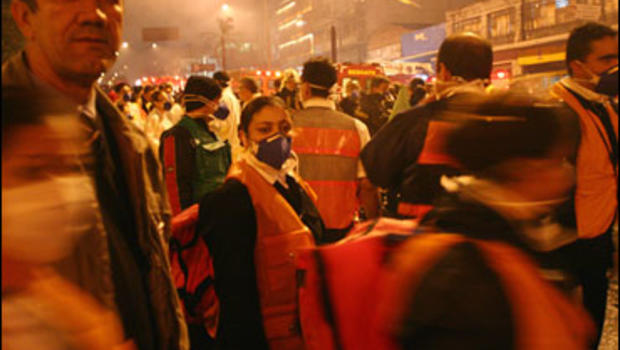 People and rescue workers stand at the site where a TAM airlines commercial jet crashed in Sao Paulo, Tuesday, July 17, 2007.