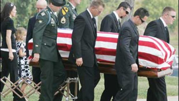 Soldiers carry the flag-draped casket of Michael Thompson after his funeral service in Kingston, Okla.