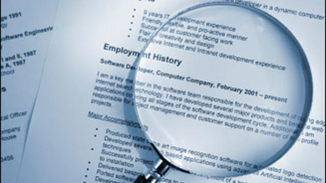 blue toned selective focus shot of resume and magnifying glass