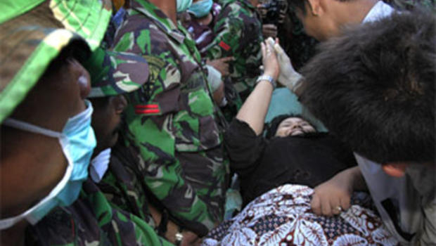 A survivor, Suci Ravika Wulan Sari, high-fives an Indonesian rescue worker as she was pulled out of a fallen building on Friday, Oct. 2, 2009 in Padang, Indonesia, after being trapped there since Wednesday's earthquake.