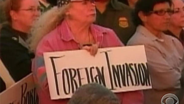 """An Arizonan holds a sign that reads, """"Foreign Invasion."""""""