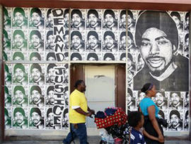 A Family Walks by Posters of Oscar Grant (AP)