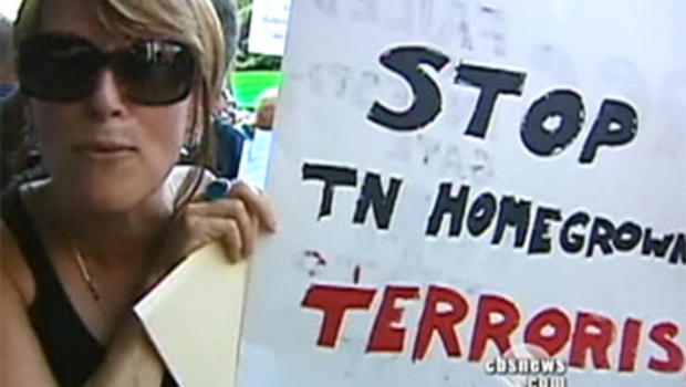 A woman holds up a sign as she attends a protest against a proposed mosque near Nashville, Tenn.