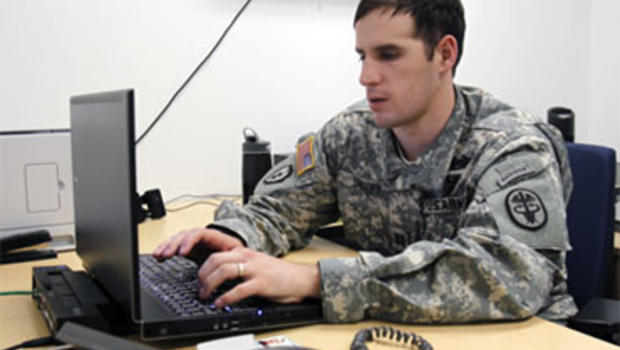 In this April 8, 2010 photo, Capt. Scott Smiley checks e-mail in his office in West Point, N.Y.