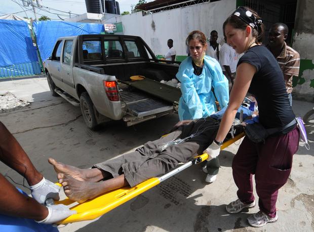 Nurses help a cholera victim into the Hospital