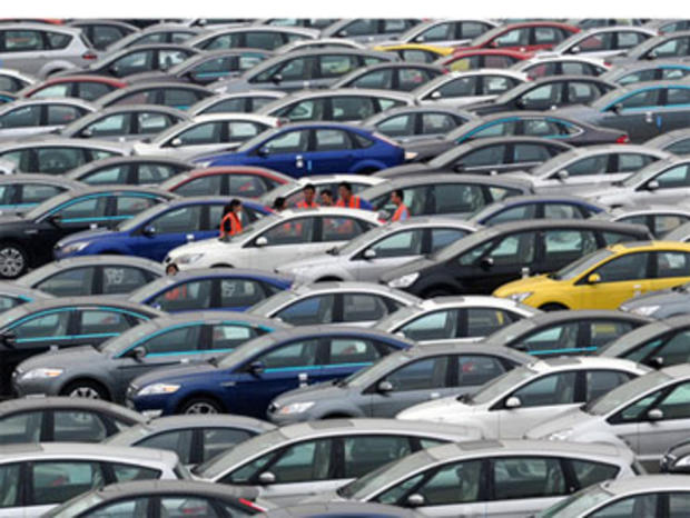 In this Aug. 25, 2010 photo, people stand near Ford cars at a plant of Changan Ford Mazda Automobile Co. in southwest China's Chongqing city.