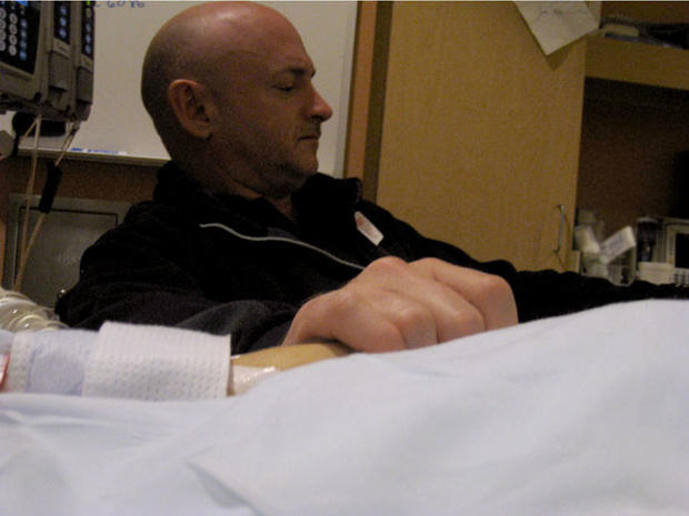 Mark Kelly holds the hand of his wife, Rep. Gabrielle Giffords, wife's hand at her bedside Sunday, Jan. 9, 2011, in the congresswoman's room at University Medical Center.