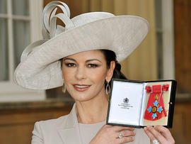 Catherine Zeta Jones poses for photographs after receiving her Commander of the Order of the British Empire (CBE) from Britain's Prince Charles at Buckingham Palace in London on Feb. 24, 2011.