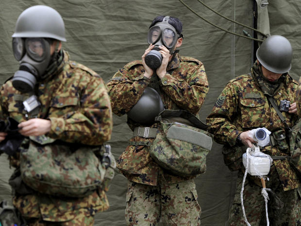 Japanese soldiers mobilize to wash radioactive material from emitted from the Fukushima nuclear power plant on March 15, 2011.