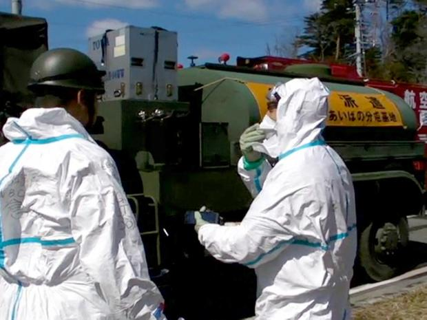 In this image taken from footage released by the Japan Defense Ministry, Japan Self-Defense Forces personnel talk before starting to spray water toward the Unit 3 of the troubled Fukushima Dai-ichi nuclear complex, Okumamachi, northeastern Japan, on Friday, March 18, 2011. Military fire trucks sprayed the reactor units Friday for a second day, with tons of water arching over the facility in attempts to prevent the fuel from overheating and emitting dangerous levels of radiation. (AP Photo/Japan Defense Ministry) EDITORIAL USE ONLY