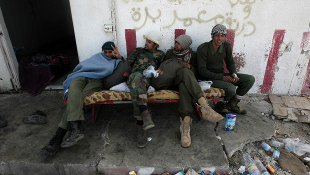 Libyan rebels rest in Uqayla, 20 kms (12 miles) east of Ras Lanuf, on March 30, 2011