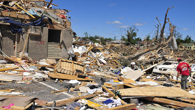 A man looks for personal items after a tornado struck Alabama.