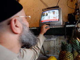man watches a TV broadcast on the death of Osama bin Laden at a vegetable shop in the southern port city of Sidon, Lebanon