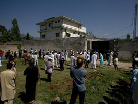 Locals gather outside the perimeter wall and sealed gate into the compound and a house where Osama bin Laden was caught and killed