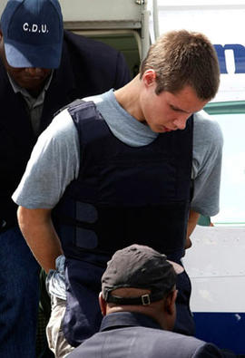 Colton Harris-Moore exits a plane handcuffed as he is escorted by police upon arrival to Nassau, Bahamas, after his arrest before dawn in northern Eleuthera island, on July 11, 2010.
