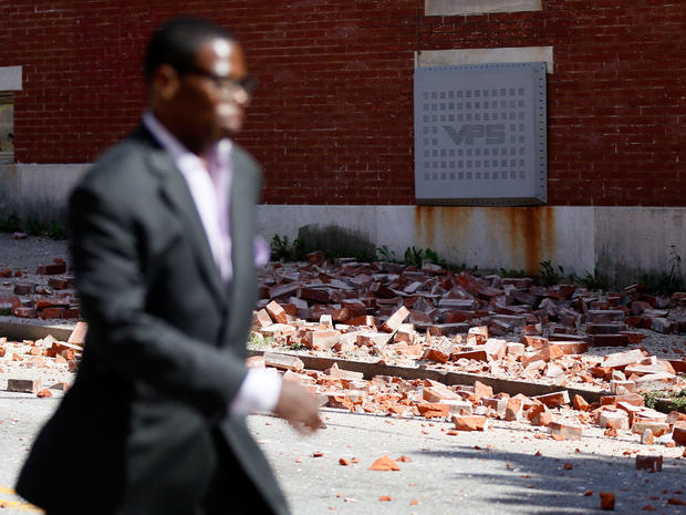 A man walks past bricks that fell off of a house once owned by the late Rep. Parren Mitchell, D-Md., after an earthquake was felt in Baltimore, Aug. 23, 2011.
