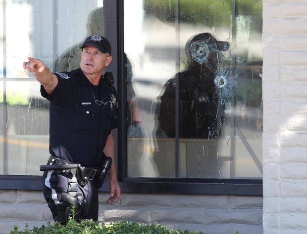 With bullet holes seen in a window, officers look for evidence at the scene of a shooting at an IHOP restaurant in Carson City, Nev. on Sept. 6, 2011.