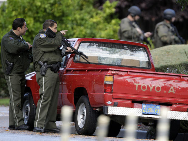 Police search a neighborhood in Cupertino, Calif., Oct. 5, 2011, looking for a shooting suspect. Authorities say a disgruntled employee opened fire at the Permanente Quarry, killing two people and wounding at least six others during a morning meeting. Later, a woman was shot in an attempted carjacking by a man matching the gunman's description, authorities said.