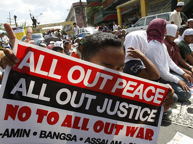 "A Filipino Muslim flashes the peace sign as he holds a placard during a ""Prayer-for-Peace"" rally near the Presidential Palace Friday Oct. 28, 2011 in Manila, Philippines."