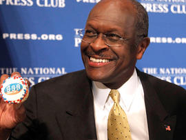 Republican presidential candidate, Herman Cain holds up a muffin that has his catch-phrase 9-9-9 tax plan printed on it, before speaking at the National Press Club in Washington, Monday, Oct. 31, 2011.
