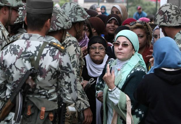 Egyptian women walk past soldiers as they arrive to vote