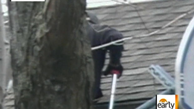 Image from undercover video provided by the National Insurance Crime Bureau shows a contractor claiming to inspect a house who's really inflicting damage he would say was caused by hail, to try to collect insurance money for fixing it.