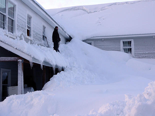 In this Saturday, Jan. 7, 2012 photo provided by the Alaska Division of Homeland Security and Emergency Management, a man stands on a house buried in snow in the fishing town of Cordova, Alaska.