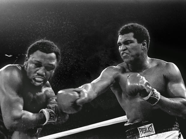 Sweat spray flies from the head of challenger Joe Frazier as Muhammad Ali connects