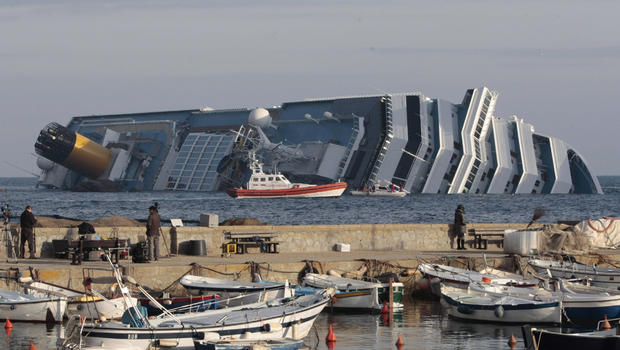People view the cruise ship Costa Concordia from the harbor wall