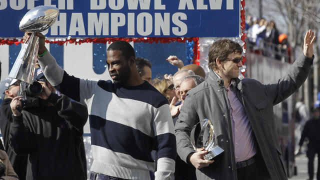 Justin Tuck holds the Vince Lombardi Trophy, and Eli Manning, holding the Halas Trophy