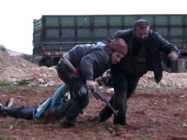 Syrian rebels drag away a wounded fighter after a battle with President Assad's military forces