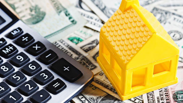 A yellow toy house sits on a background of many US dollars, next to a calculator.