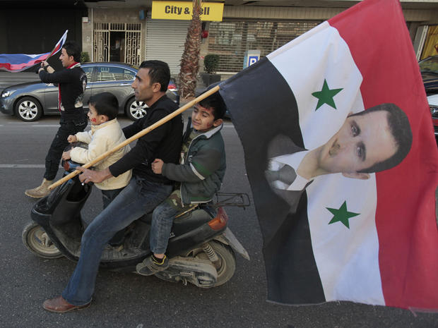 Pro-Syrian regime protester rides his scooter with his two sons in Beirut, Lebanon