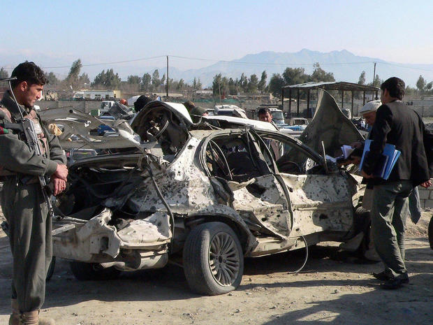 Afghan police keep watch as locals inspect the site of a suicide attack in Jalalabad