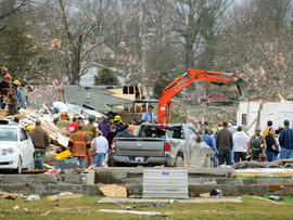 Emergency responders work to clear debris in a neighborhood in Harrisburg, Ill., after an early morning tornado Wednesday, Feb. 29, 2012.