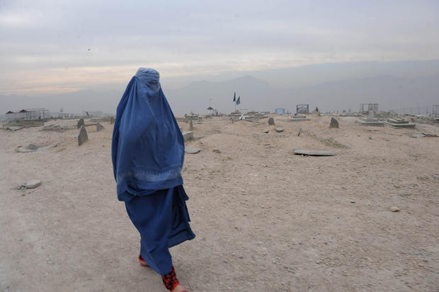 A burqa-clad Afghan woman walks in a cemetery Kabul on November 23, 2011.