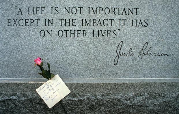 A single rose with a handwritten note rests at the grave of baseball Hall-of-Famer Jackie Robinson