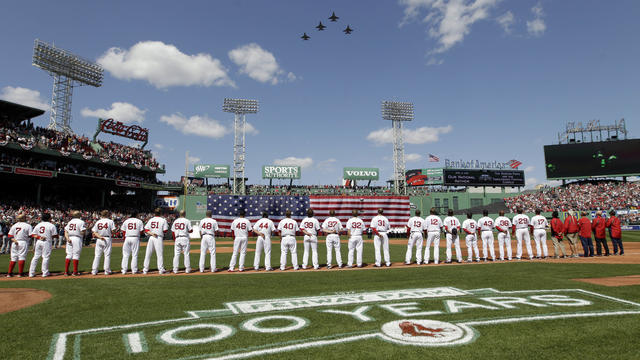Boston Red Sox players line up for the national anthem as fighter jets from the Vermont National Guard fly over Fenway Park