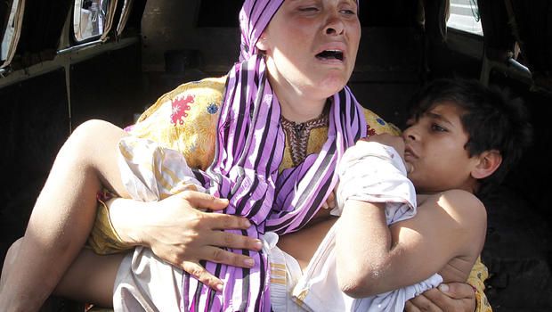 A Syrian woman cries as she carries her injured son, who was shot in the hand by a Syrian border guard when they were crossing a river from Syria to Lebanon, at the northern Lebanese-Syrian border town of Wadi Khaled, Lebanon, May 30, 2012.
