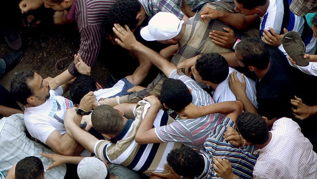 Supporters of Muslim Brotherhood presidential candidate Mohamed Morsi scramble to beat-up who they claim is a thug as they gathered in Cairo's Tahrir Square on June 22, 2012 to denounce a power grab by the ruling military.