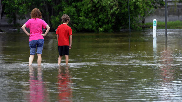 People walk through floodwaters left by Tropical Storm Debby on Anna Maria Island, Fla., Monday