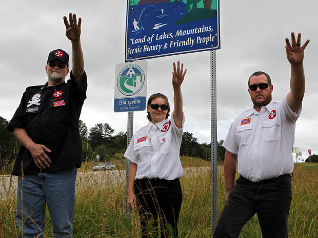 Knighthawk (from left), April Hanson and her husband Harley Hanson, members of the International Keystone Knights Realm of Georgia, perform a traditional Klan salute along the portion of highway they want to adopt .