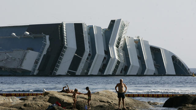 Tourists relax on rocks in front of the Costa Concordia wreckage