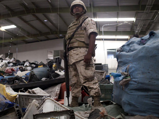 A Mexican army soldier stands inside a warehouse used for recycling assorted materials where an incomplete cross-border illegal tunnel was found underneath a bathroom sink by the Mexican army in Tijuana, Mexico, July 12, 2012.