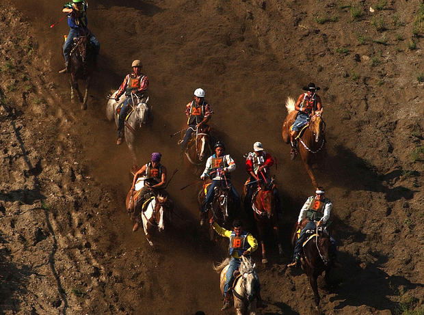 Participants in the Omak Suicide Race ride down a 62-degree slope to the Okanogan River August 15, 2004 in Omak, Washington.