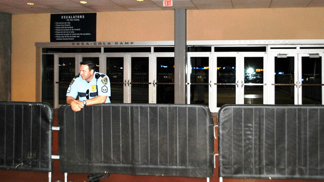 Police block the exit to an escalator where a football fan fell and died at Reliant Stadium while attending an NFL preseason game between the Houston Texans and the Minnesota Vikings in Houston Aug. 30, 2012.