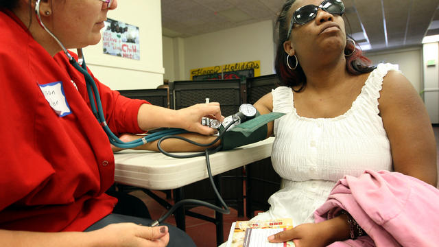 Nurse Allison Miller, left, checks the blood pressure of Keri Anderson as nurses and physicians give free basic health screenings to call attention to what they say is an ongoing health care emergency July 10, 2012, in Los Angeles.