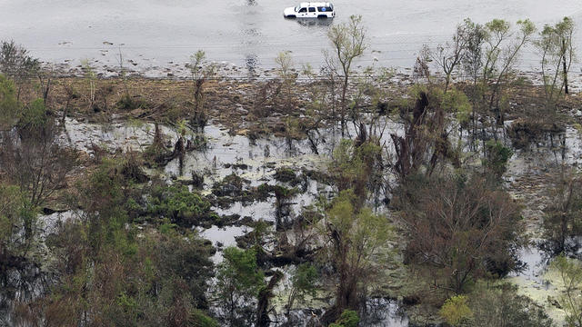 Aerial photo shows car in floodwaters in aftermath of Hurricane Isaac. in Plaquemines Parish, La., Wednesday. Several miles of coastline were tarred with weathered oil washing ashore days after Isaac raked Gulf Coast.