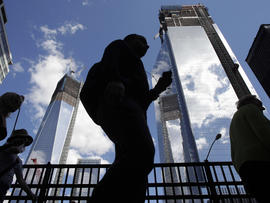 Visitors to the National September 11 Memorial walk below the rising towers 1 World Trade Center, left, and 4 World Trade Center, Monday, Sept. 10, 2012 in New York. Tuesday will mark the eleventh anniversary of the attacks of Sept. 11, 2001.